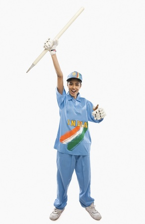 triumphing: Portrait of a female cricketer holding a cricket stump and cheering
