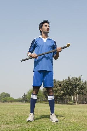 Man met een hockeystick in een veld