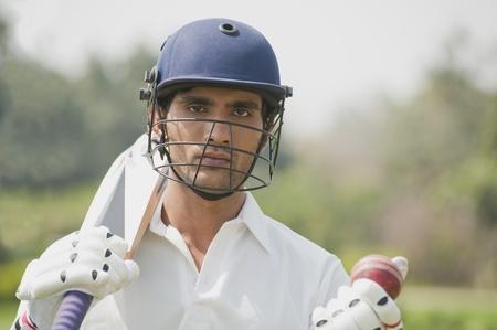 cricket bat: Cricket batsman holding a cricket bat with a cricket ball LANG_EVOIMAGES