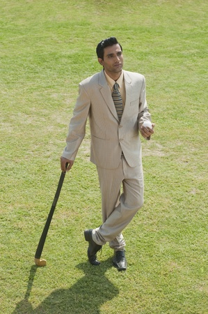 Businessman holding a hockey stick and a ball in a field