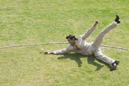 cricket field: Businessman diving to stop a ball near boundary line in a cricket field LANG_EVOIMAGES