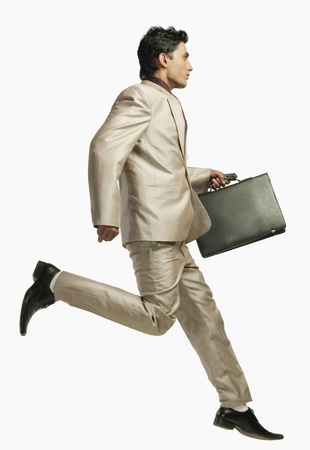 getting late: Businessman running with a briefcase LANG_EVOIMAGES