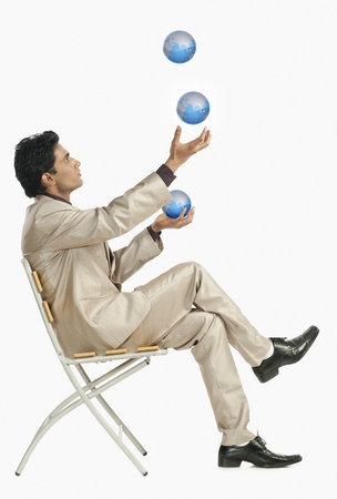world at your fingertips: Businessman sitting on a chair and juggling with globes LANG_EVOIMAGES