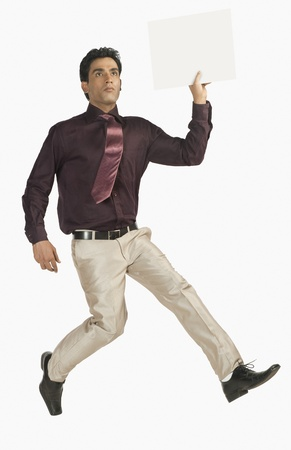 getting late: Businessman running with a blank placard