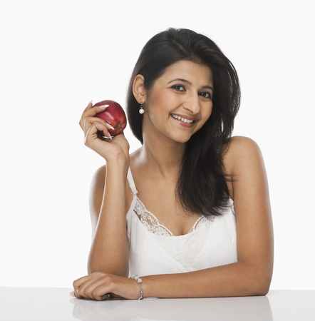 Woman holding an apple and smiling 免版税图像