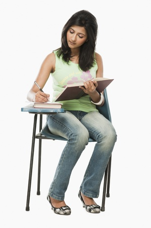 University student taking notes in a classroom Stock Photo - 10168605