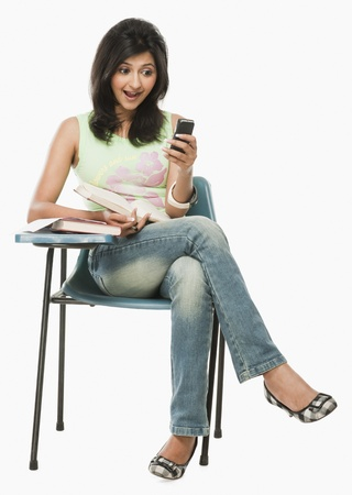 clipping  messaging: University student looking at a mobile phone with surprise LANG_EVOIMAGES