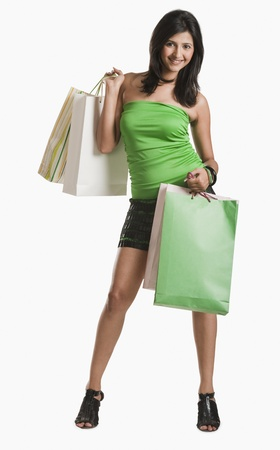 Portrait of a woman carrying shopping bags and smiling Stock Photo - 10168881