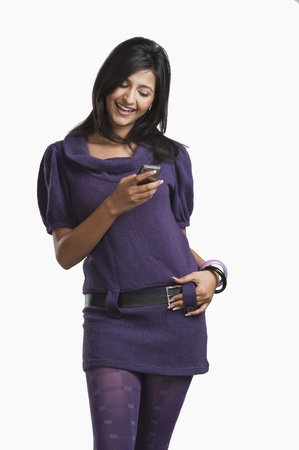 clipping  messaging: Woman text messaging on a mobile phone and smiling LANG_EVOIMAGES