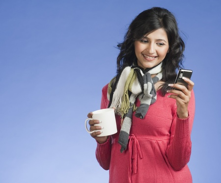 clipping  messaging: Woman holding a cup of coffee and text messaging on a mobile phone