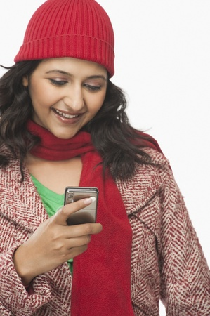 clipping  messaging: Woman reading a message on a mobile phone and smiling LANG_EVOIMAGES