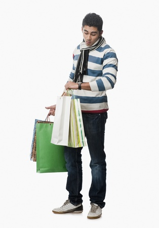 Man checking the time and carrying shopping bags Stock Photo - 10166895