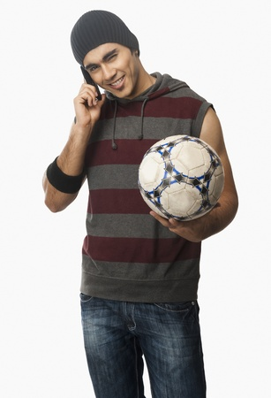 Man talking on a mobile phone and holding a soccer ball Stock Photo - 10167385