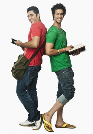 indian subcontinent ethnicity: Two university students reading books back to back LANG_EVOIMAGES