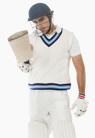 batsman: Portrait of a cricket batsman showing his bat LANG_EVOIMAGES