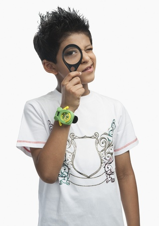 Portrait of a boy looking through a magnifying glass