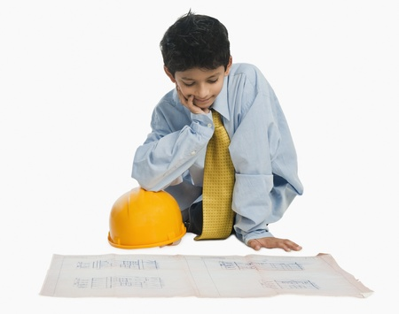 Boy dressed as an architect and working on a blueprint Imagens