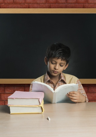 Boy imitating a teacher and reading a book in a classroom