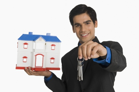 Real estate agent holding house keys and a model home