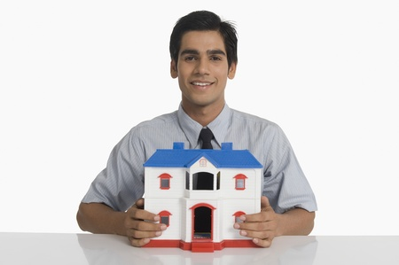 Real estate agent holding a model home and smiling