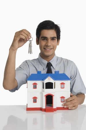 Real estate agent holding keys and a model home