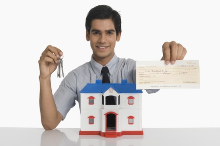 real estate investment: Real estate agent showing keys and a check near a model home