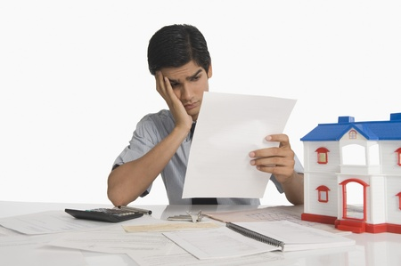 problem: Real estate agent reading a document near a model home LANG_EVOIMAGES
