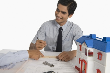 Real estate agent discussing a document with a customer