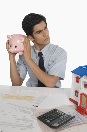 Real estate agent holding a piggy bank near his ear Stock Photo - 10167380
