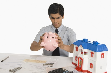 Real estate agent looking into a piggy bank Stock Photo - 10167014