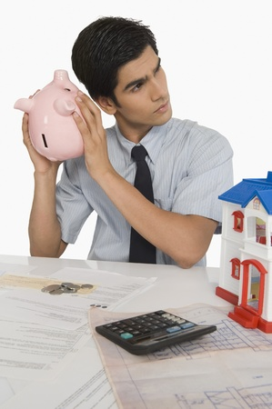 Real estate agent holding a piggy bank near his ear Stock Photo - 10167479