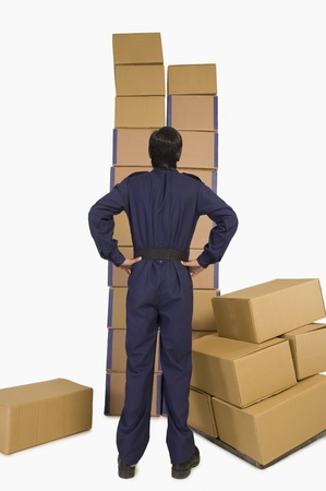 Rear view of a store incharge looking at cardboard boxes Stock Photo - 10167017