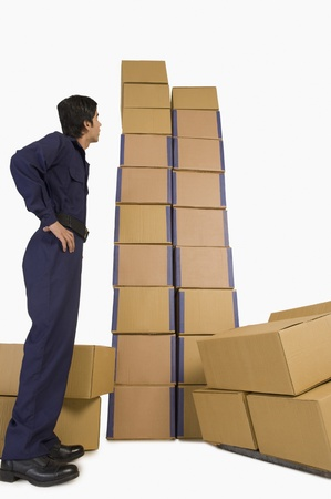 Rear view of a store incharge looking at cardboard boxes Stock Photo - 10168587