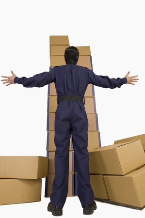 Rear view of a store incharge looking at a stack of cardboard boxes with his arm outstretched Stock Photo - 10168703