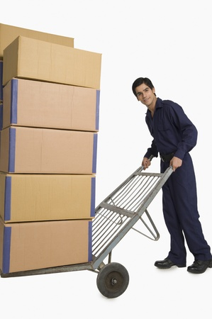 store incharge: Storekeeper carrying cardboard boxes on a hand truck LANG_EVOIMAGES