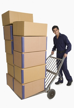 Storekeeper carrying cardboard boxes on a hand truck Stock Photo - 10167214