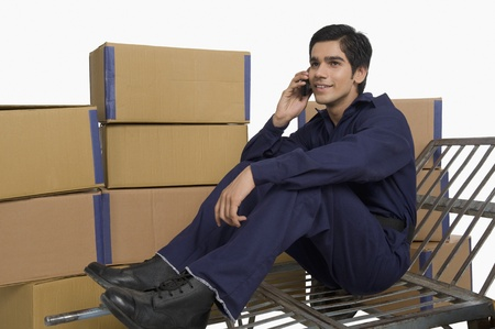 store incharge: Store incharge sitting on a hand truck and talking on a mobile phone
