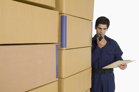 Store incharge talking on a walkie-talkie in a warehouse Stock Photo - 10167537