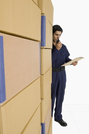 Store incharge talking on a walkie-talkie in a warehouse Stock Photo - 10168452