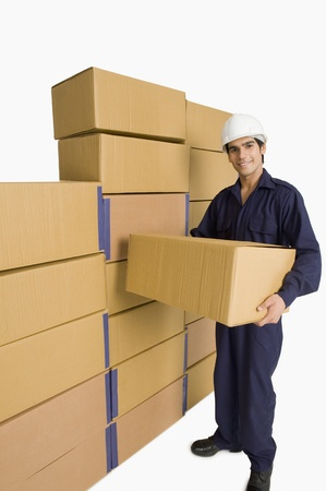 store incharge: Store incharge carrying a cardboard box in a warehouse