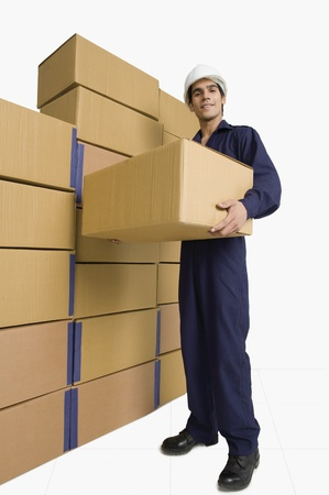 storage box: Store incharge carrying a cardboard box in a warehouse