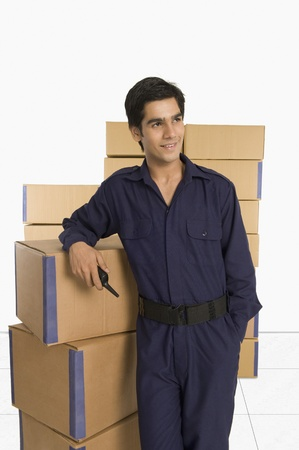 store incharge: Store incharge leaning against cardboard boxes in a warehouse LANG_EVOIMAGES