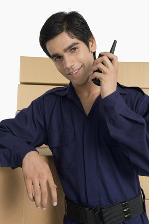 store incharge: Store incharge talking on a walkie-talkie in a warehouse