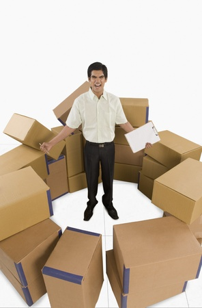 store incharge: Store incharge standing among cardboard boxes and shouting