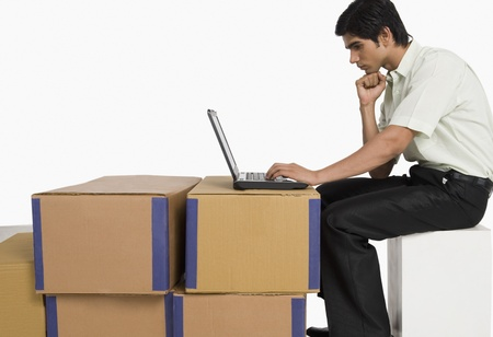 Store incharge using a laptop in a warehouse