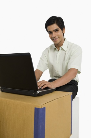 store incharge: Store incharge using a laptop in a warehouse