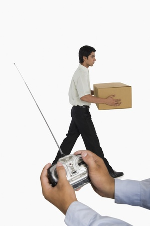 Person's hands controlling a worker with a remote control Stock Photo - 10166730