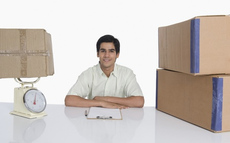 Store incharge at desk with a weight scale and cardboard boxes Stock Photo - 10168554