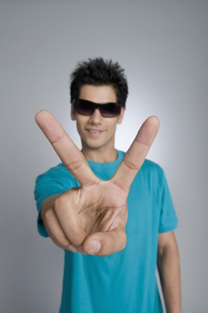 Close-up of a man showing victory sign Stock Photo - 10168340