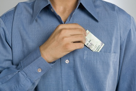 putting money in pocket: Mid section view of a man putting money in shirt pocket